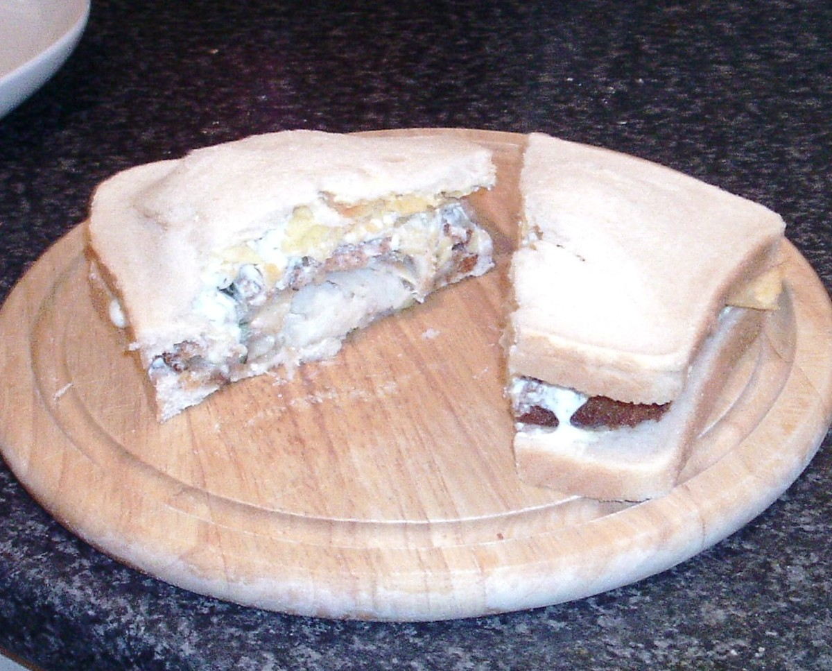 Cod, tzatziki sauce and crisps sandwich is cut to serve