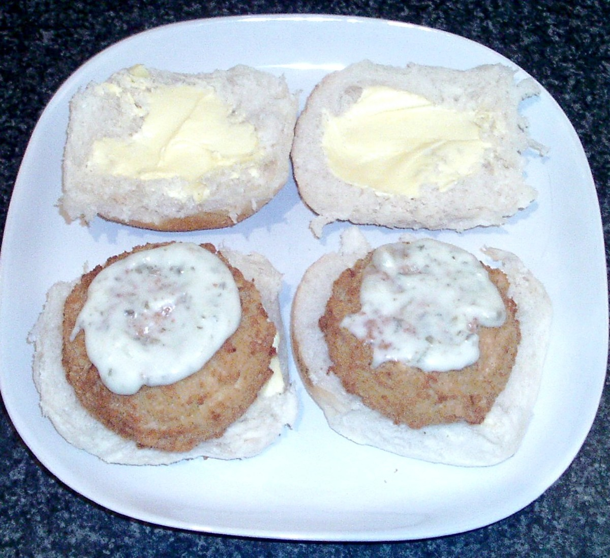Tartare sauce is spread on smoked haddock fishcakes
