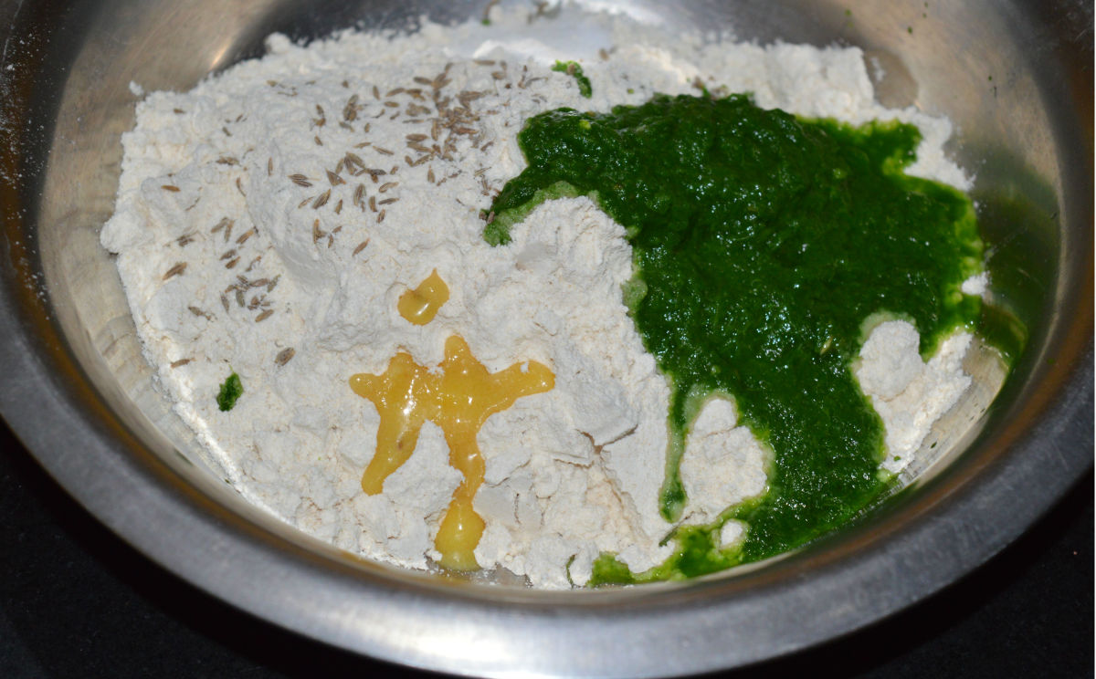 Step two: Place wheat flour in a large bowl. Add spinach puree, cumin seeds, ghee or oil, and salt. Knead, adding water little by little, to get a smooth and firm dough.