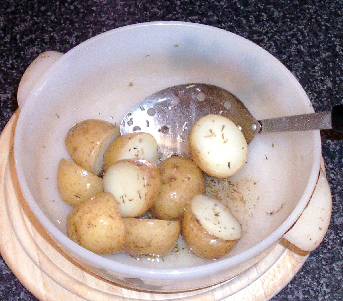 Potatoes and dried herbs are turned in hot oil