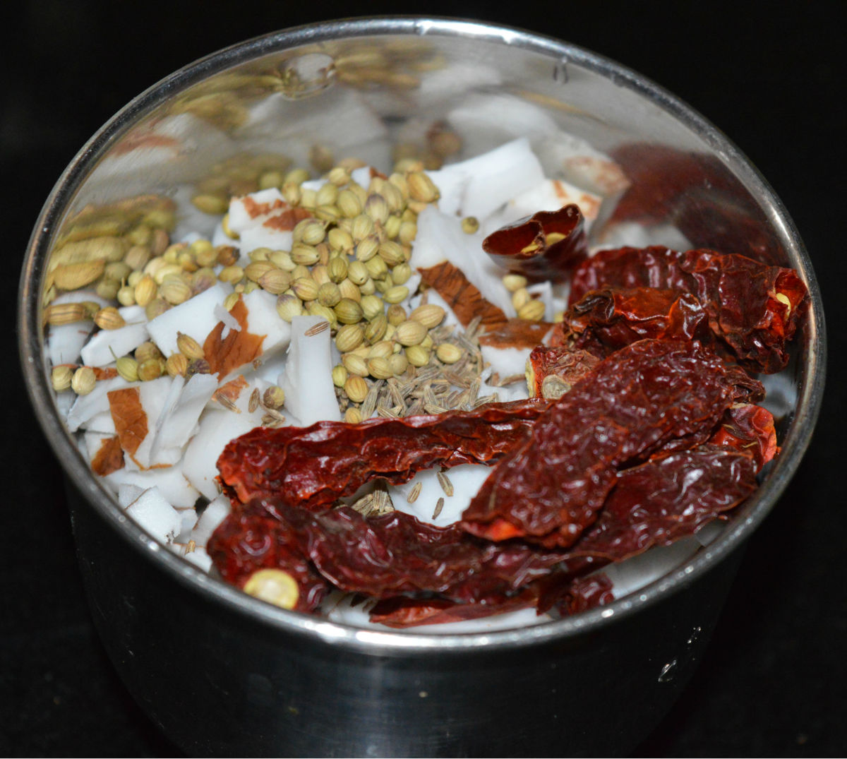 Step three: In the meanwhile, make masala paste for the gravy. Take grated coconut, cumin seeds, coriander seeds, dry red chilies, hing powder, and raw rice in a mixer jar. Grind, adding water to get a near-smooth paste.