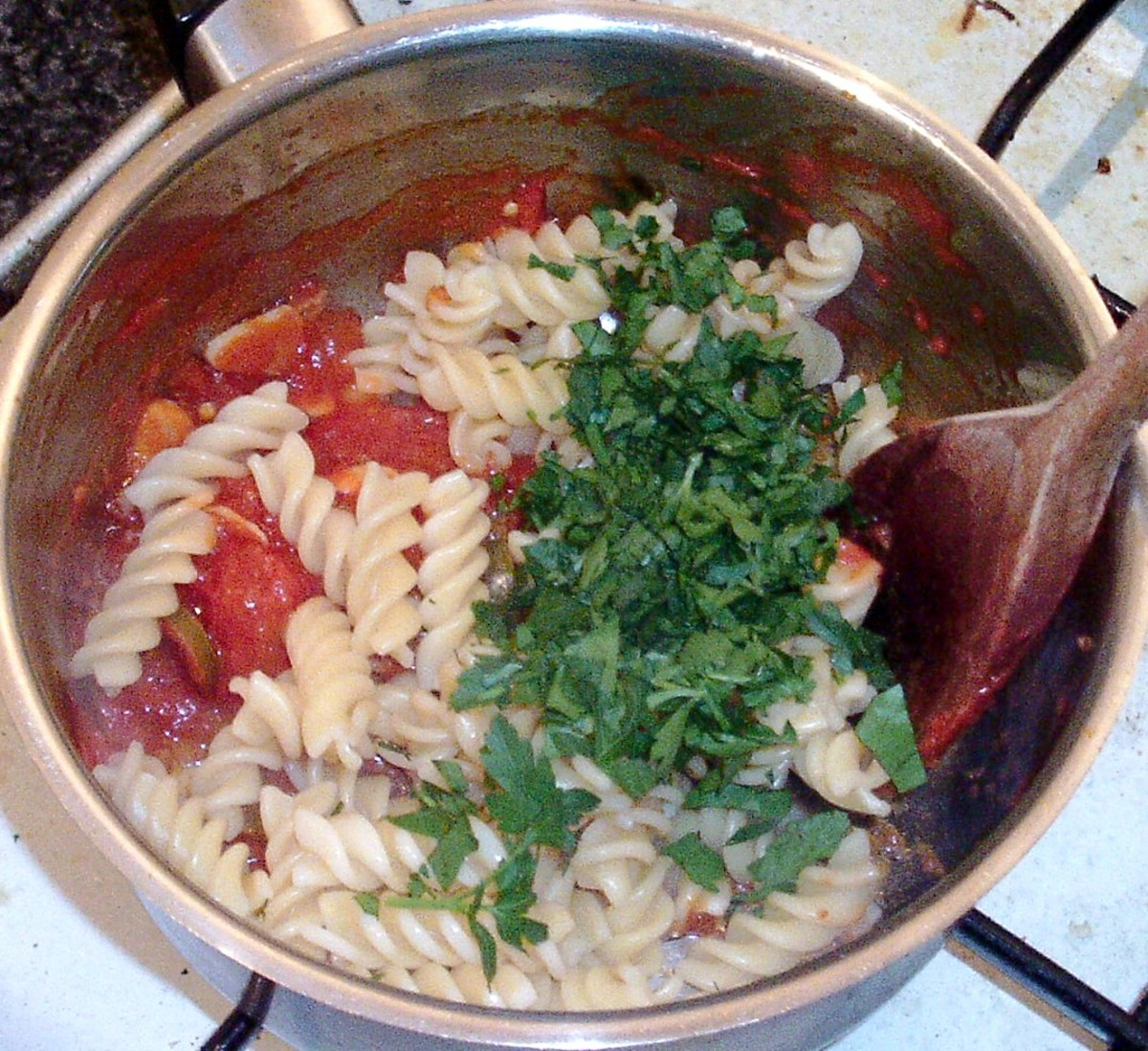 Drained pasta and chopped parsley are added to sauce