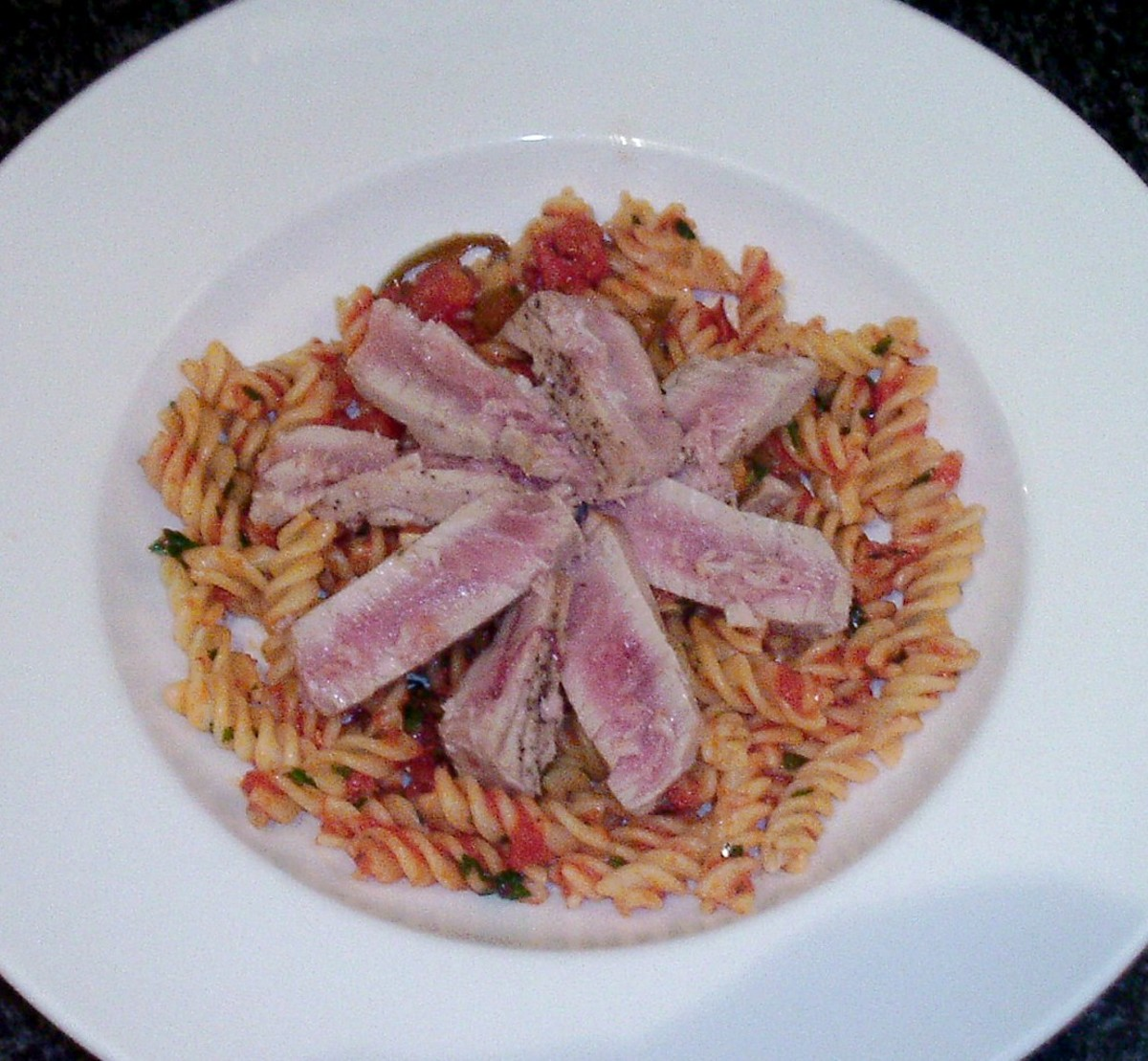 Sliced tuna is arranged on spicy tomato fusilli pasta bed