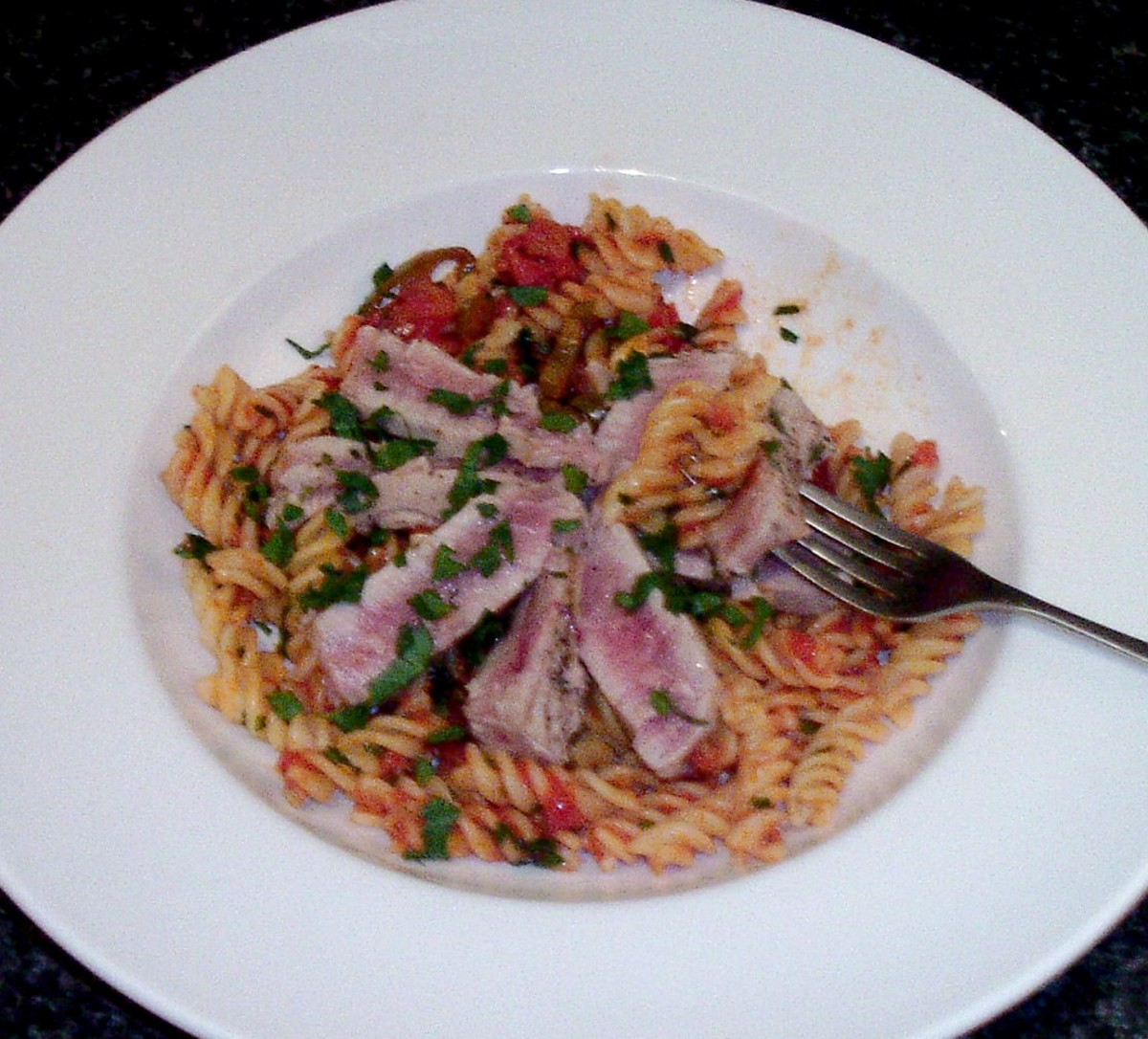Enjoying seared tuna fillet with spicy tomato fusilli pasta