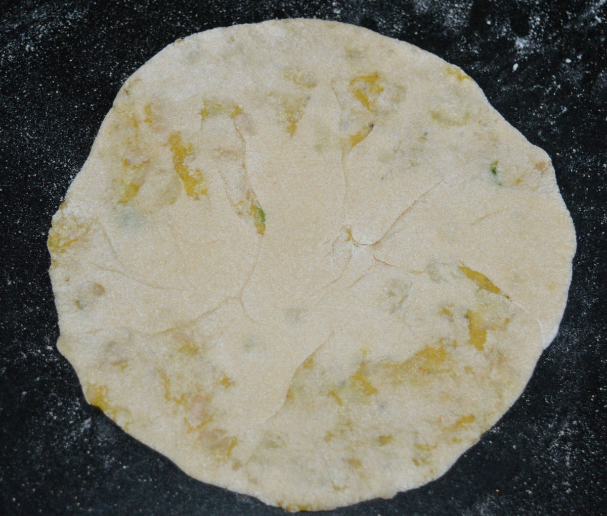 Step five: Place a portion of the stuffing in the center. Bring the edges of the disc together and close the open ends. Press it a little. Dust it with wheat flour and roll it to make a disc of about 7-8 inch diameter.