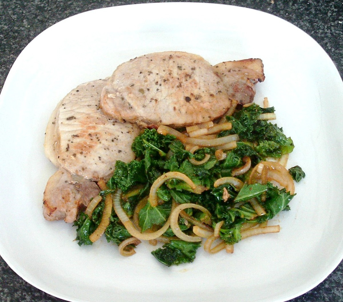 Pan fried tender pork loin fillets are served with kale and onion sauteed in their juices