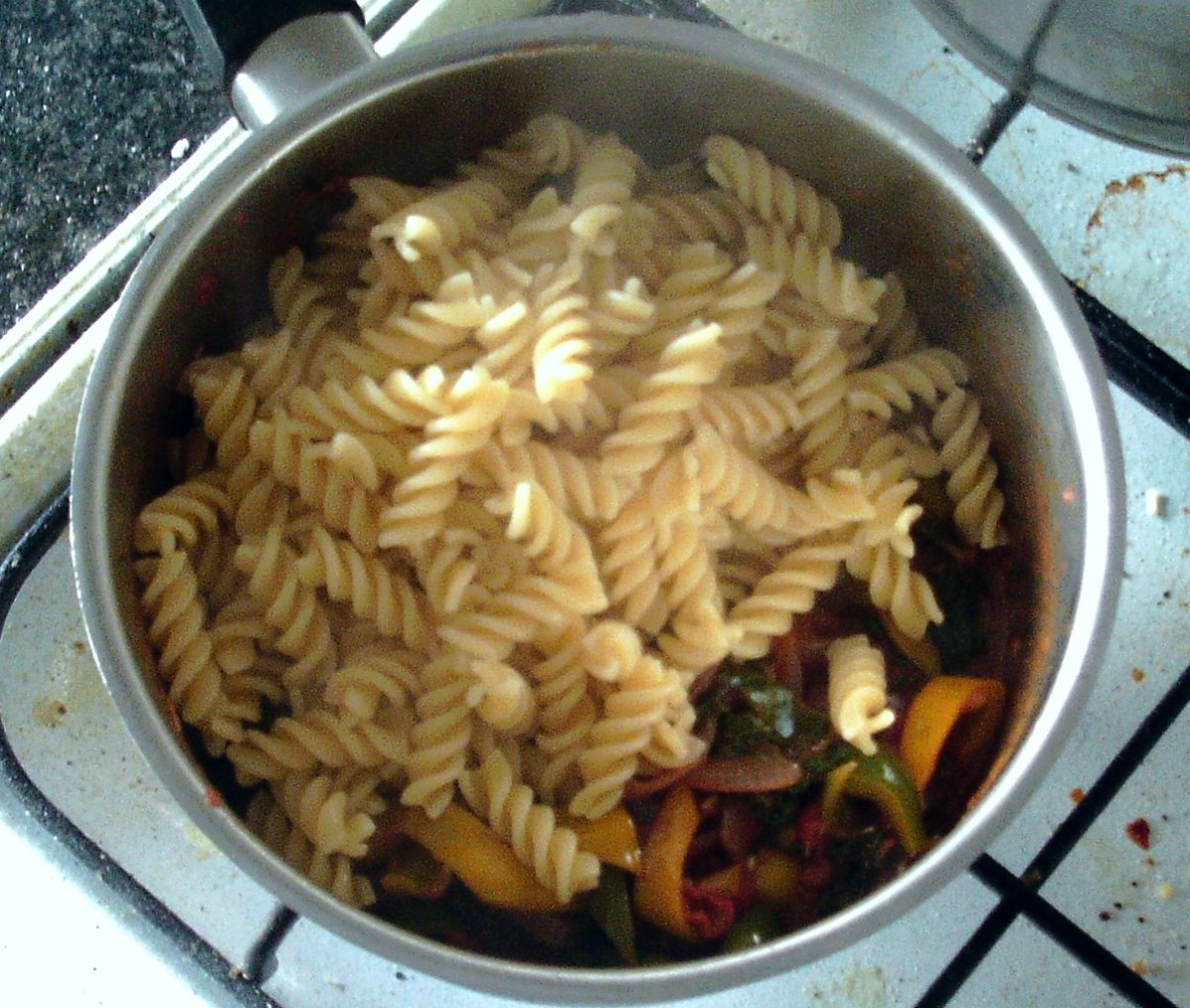 Cooked and drained pasta is added to sauce