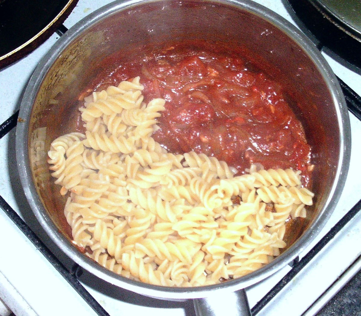 Pasta is added to spicy tomato sauce