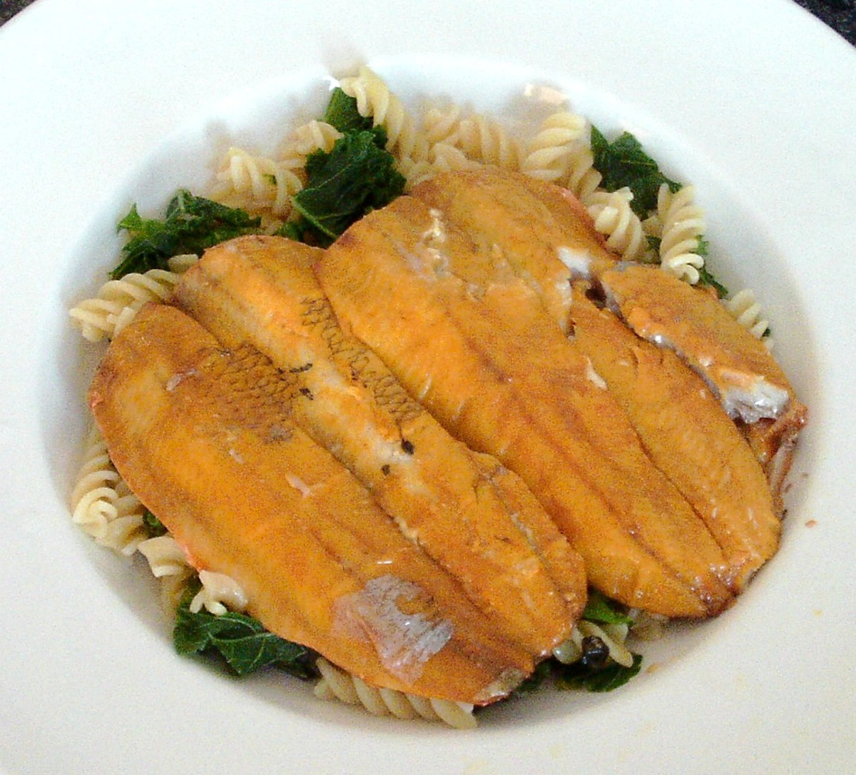 Boil in the bag kippers are served on a bed of curly kale and pasta