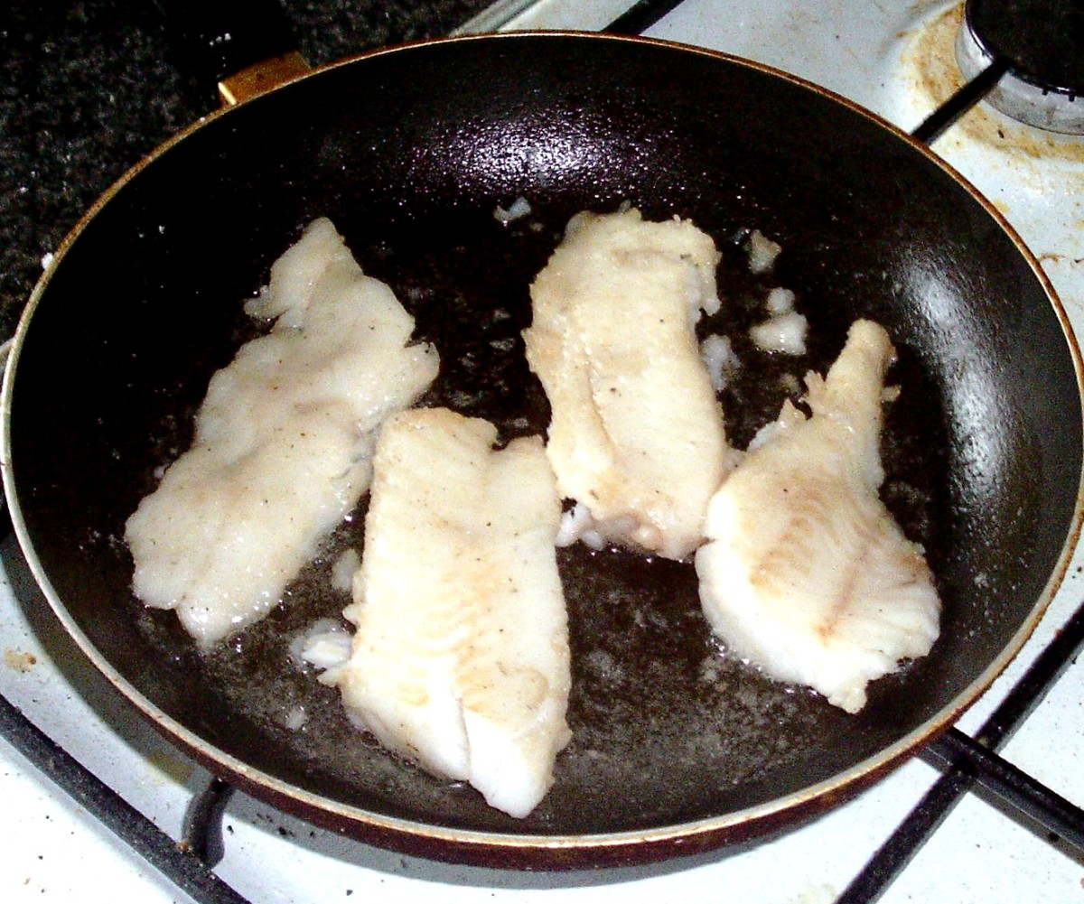 Whiting fillets are turned in the pan