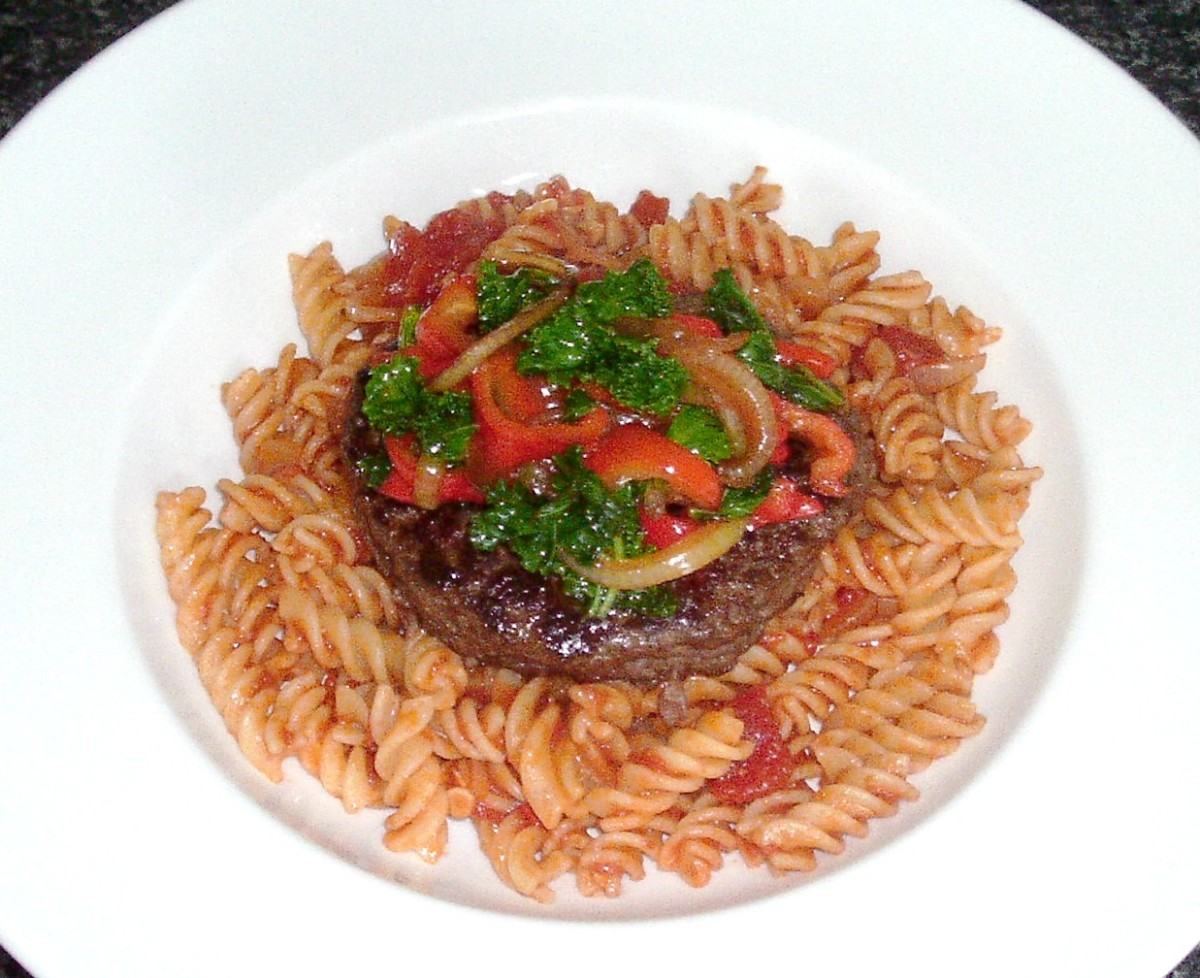 Ostrich burger on a pasta in spicy sauce bed with sauteed kale and peppers