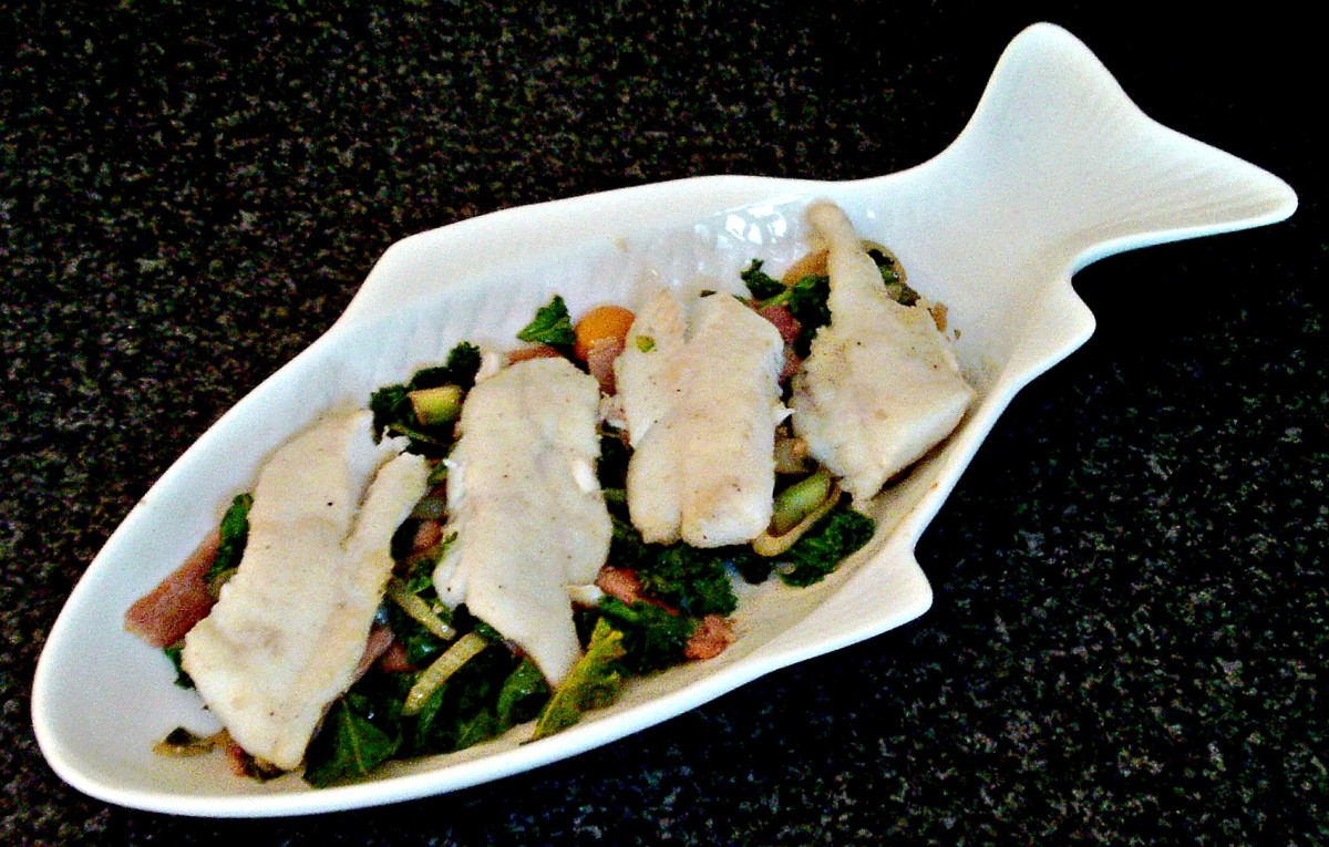 Pan fried fillets of whiting are served on a spicy bed of sauteed kale and bacon