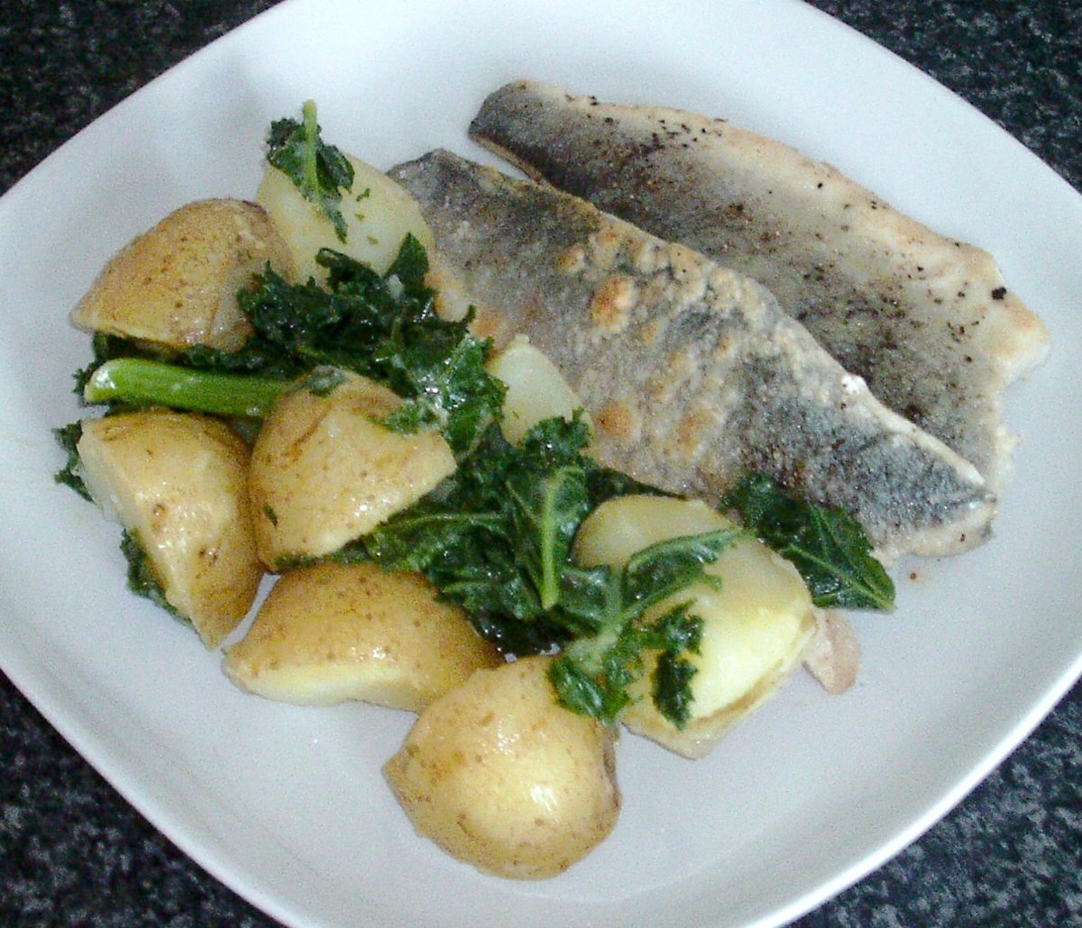 Pan fried sea bass fillets are served with boiled potatoes and kale in a rich and tasty turmeric and tarragon butter sauce