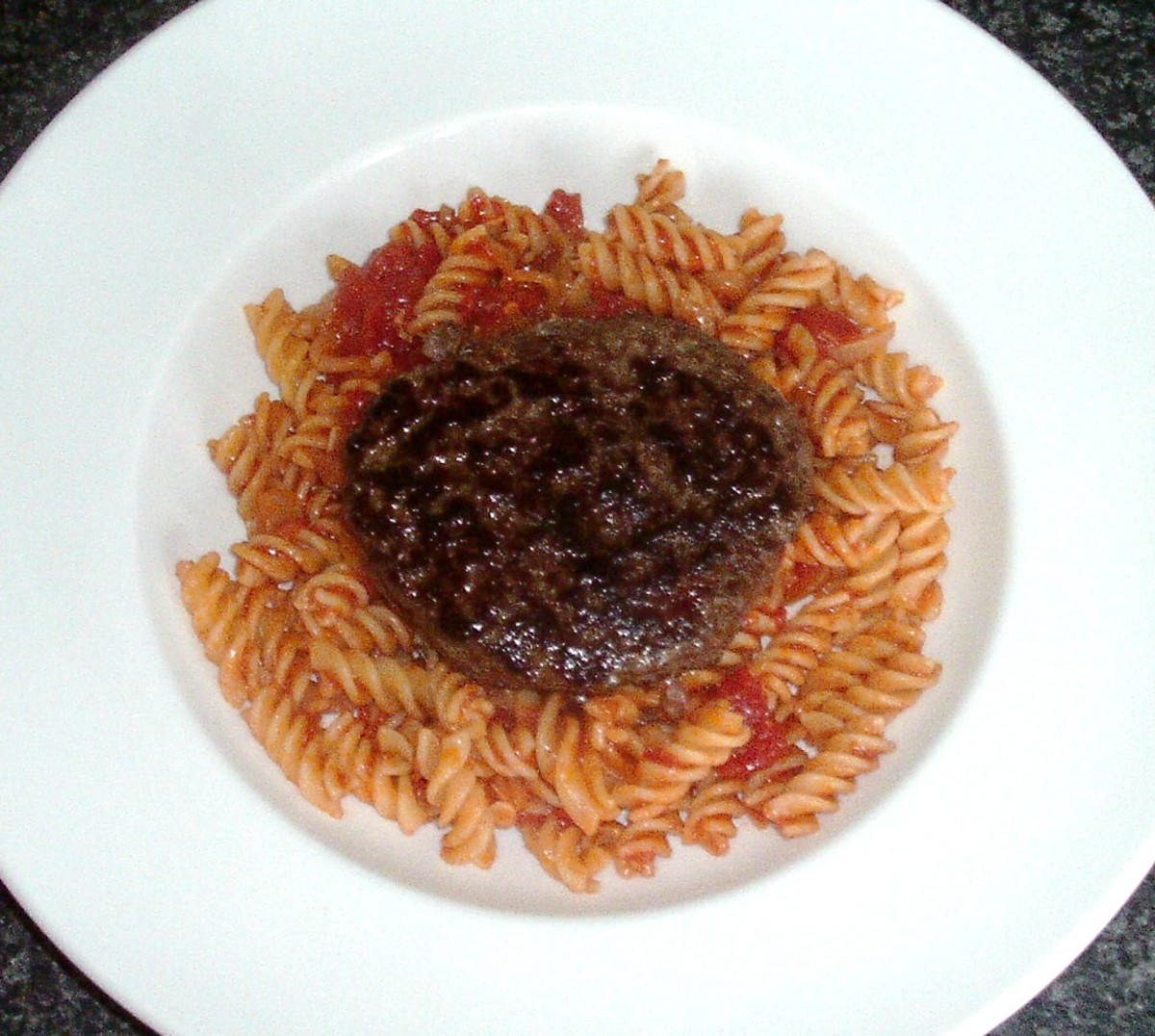 Ostrich burger is laid on spicy pasta bed