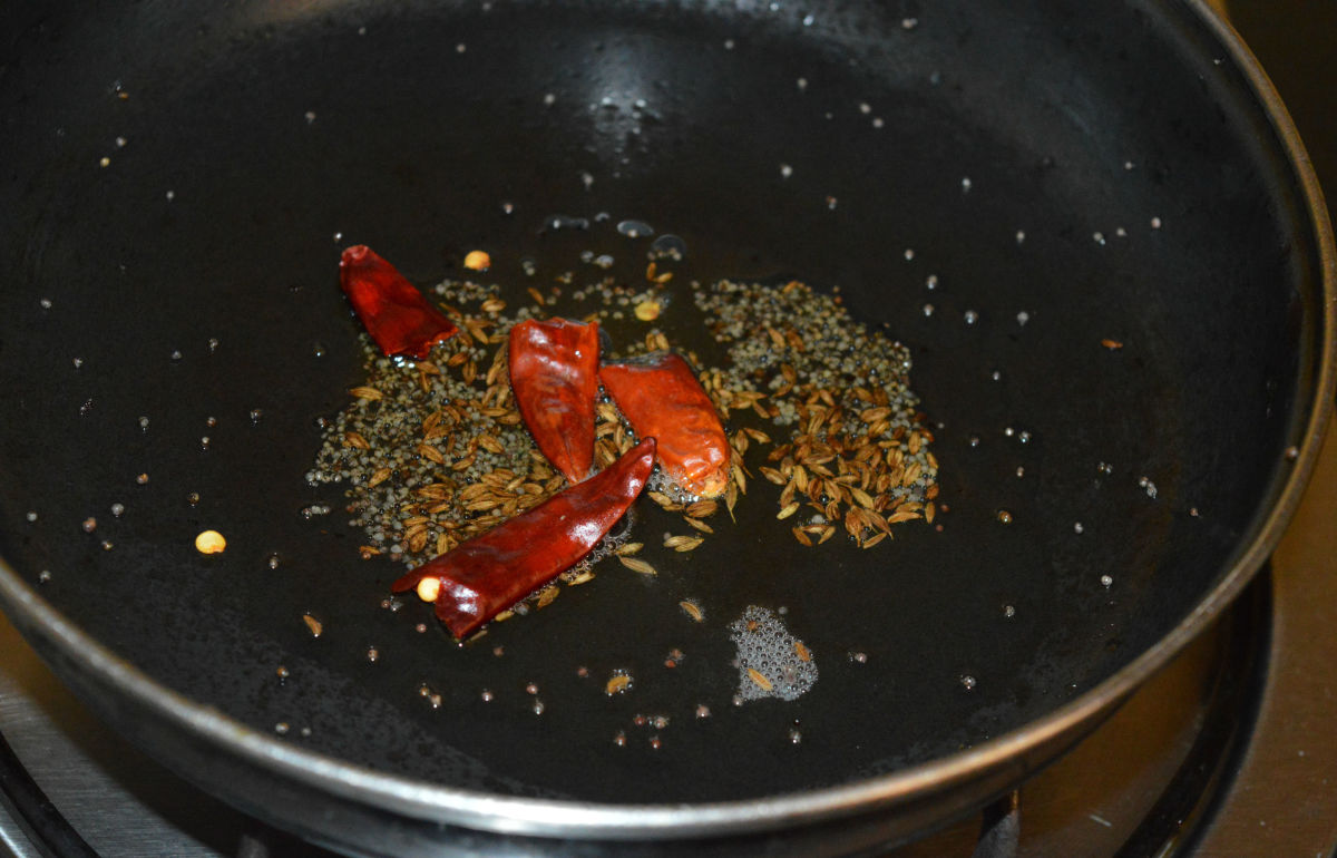 Step one: Heat oil in a deep-bottomed pan. Throw in mustard seeds and cumin seeds. Let them crackle and pop up. Add broken dry red chilies. Saute for 1-2 seconds.