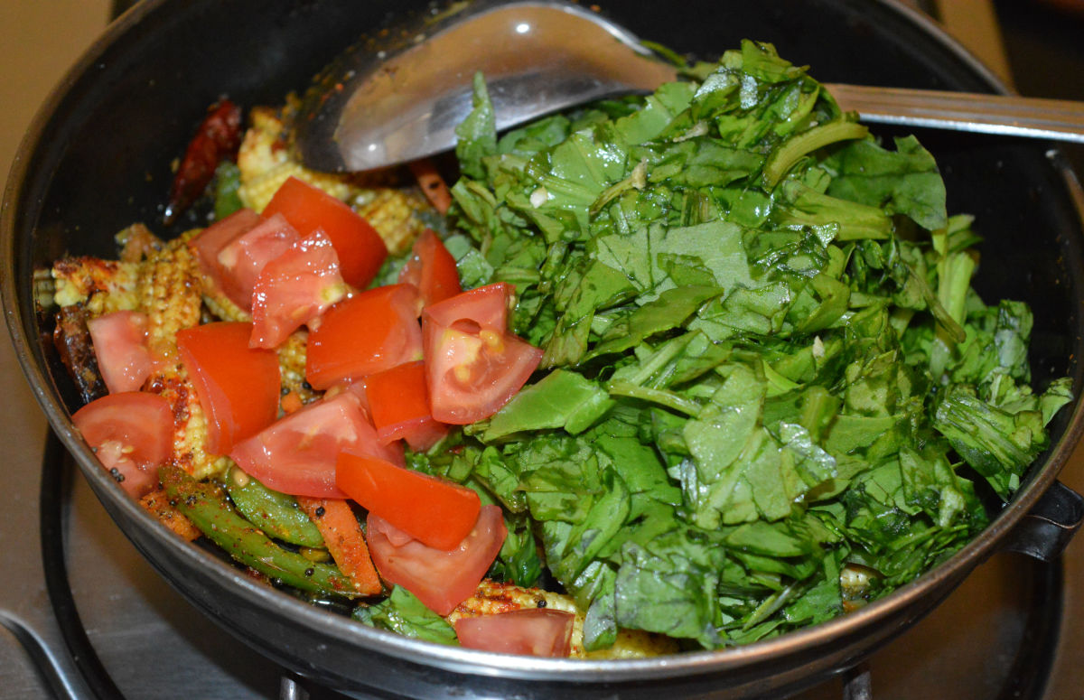Step four: Throw in chopped spinach and tomatoes. Saute until they are cooked.