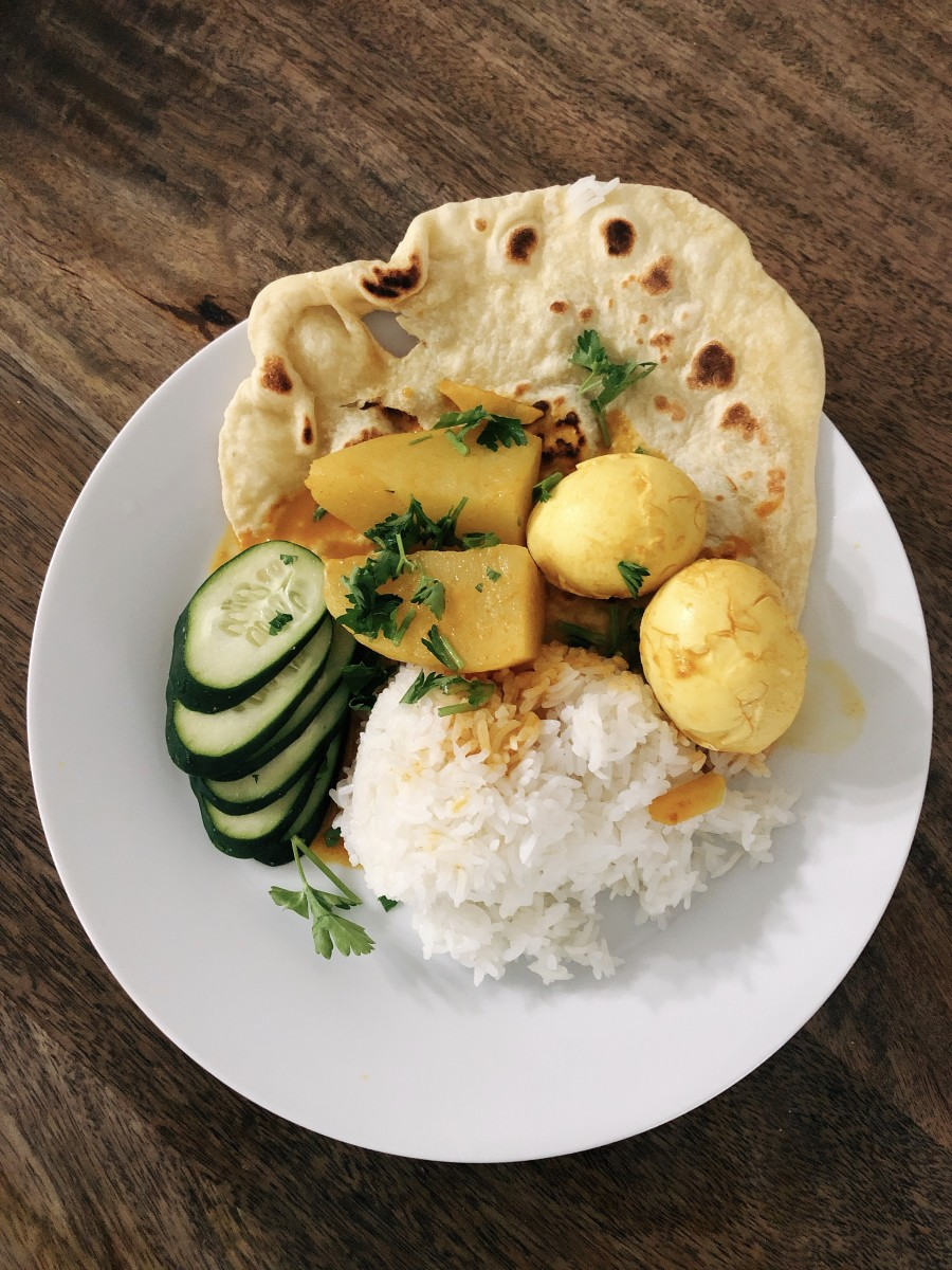 Yummy egg curry with steamed jasmine rice, homemade naan bread, and freshly cut cucumber.