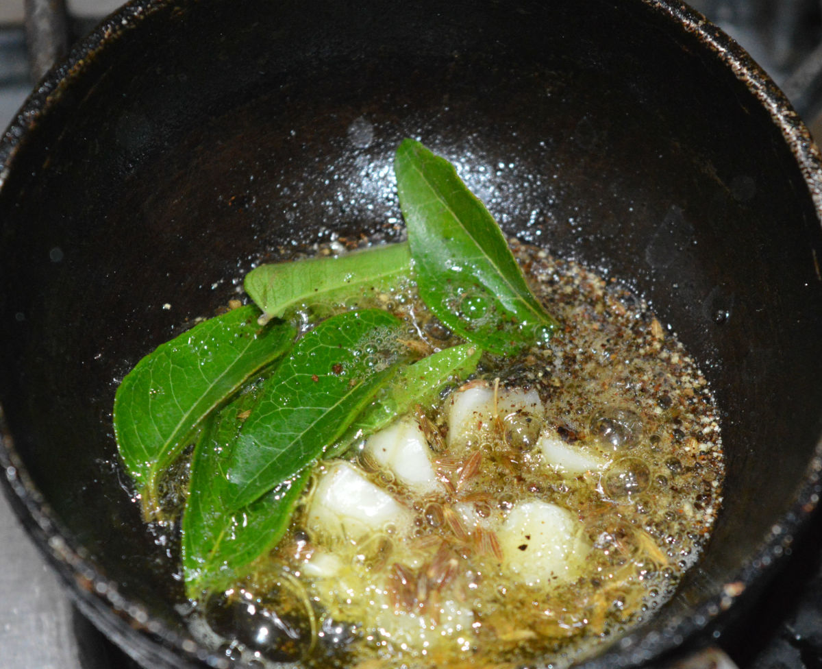 Step three: To make the seasoning, add ghee or oil, garlic cloves, asafetida powder, curry leaves, and pepper powder to a pan. Saute until the garlic becomes brownish. Turn off the heat and transfer it to the vessel containing moong dal rasam.