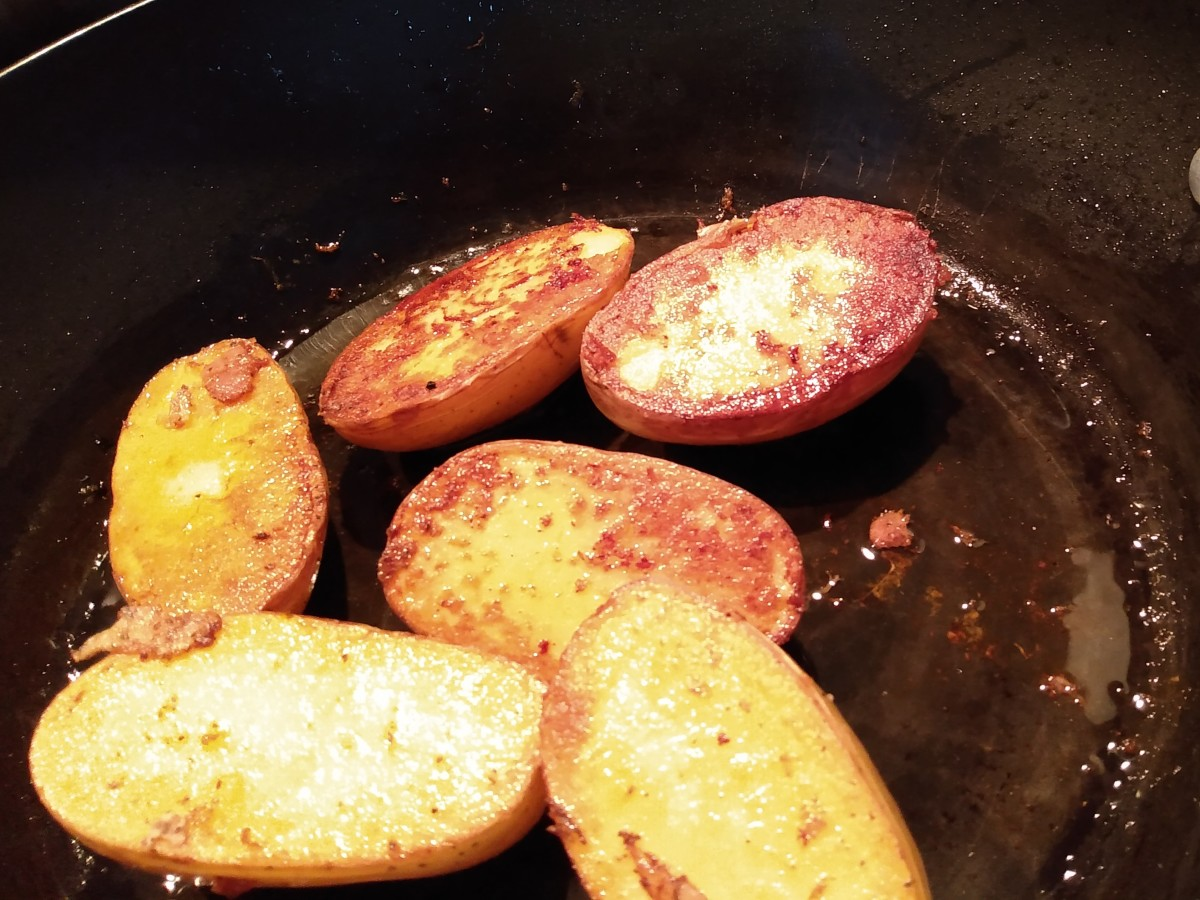 Yukon gold potatoes sliced in half vertically. One side has been sauteed. Look at that rich golden brown color.
