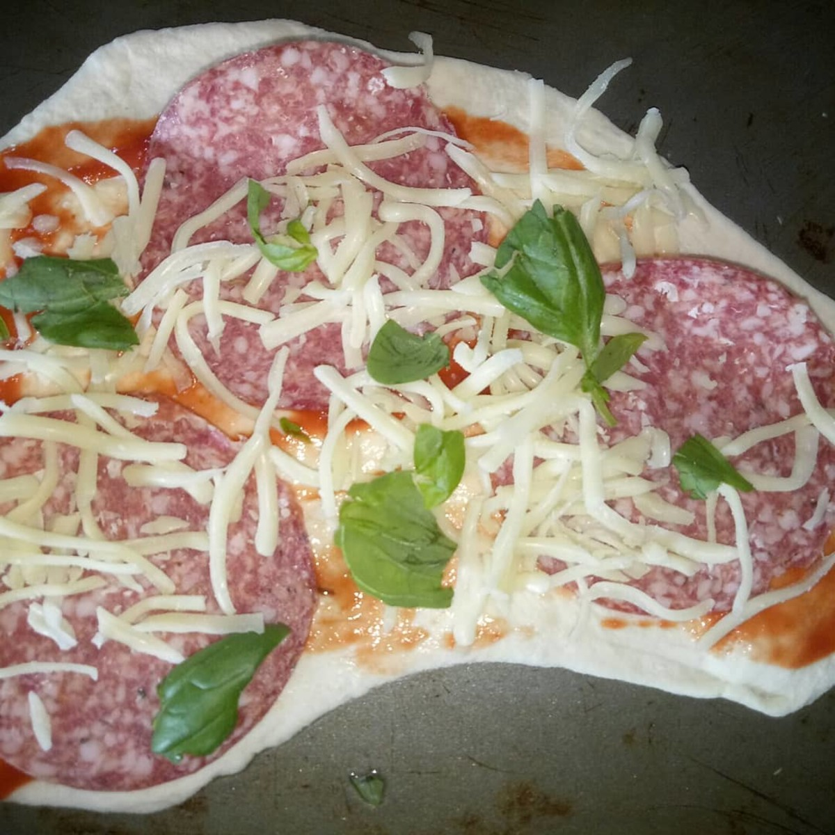Salami, cheddar and basil pizza ready to go into the oven.