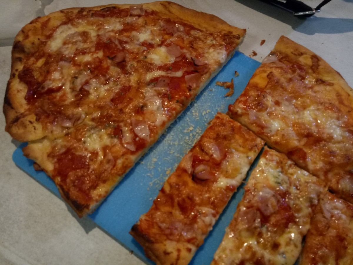 Larger, family-style pizza cooked and cut ready to be eaten.
