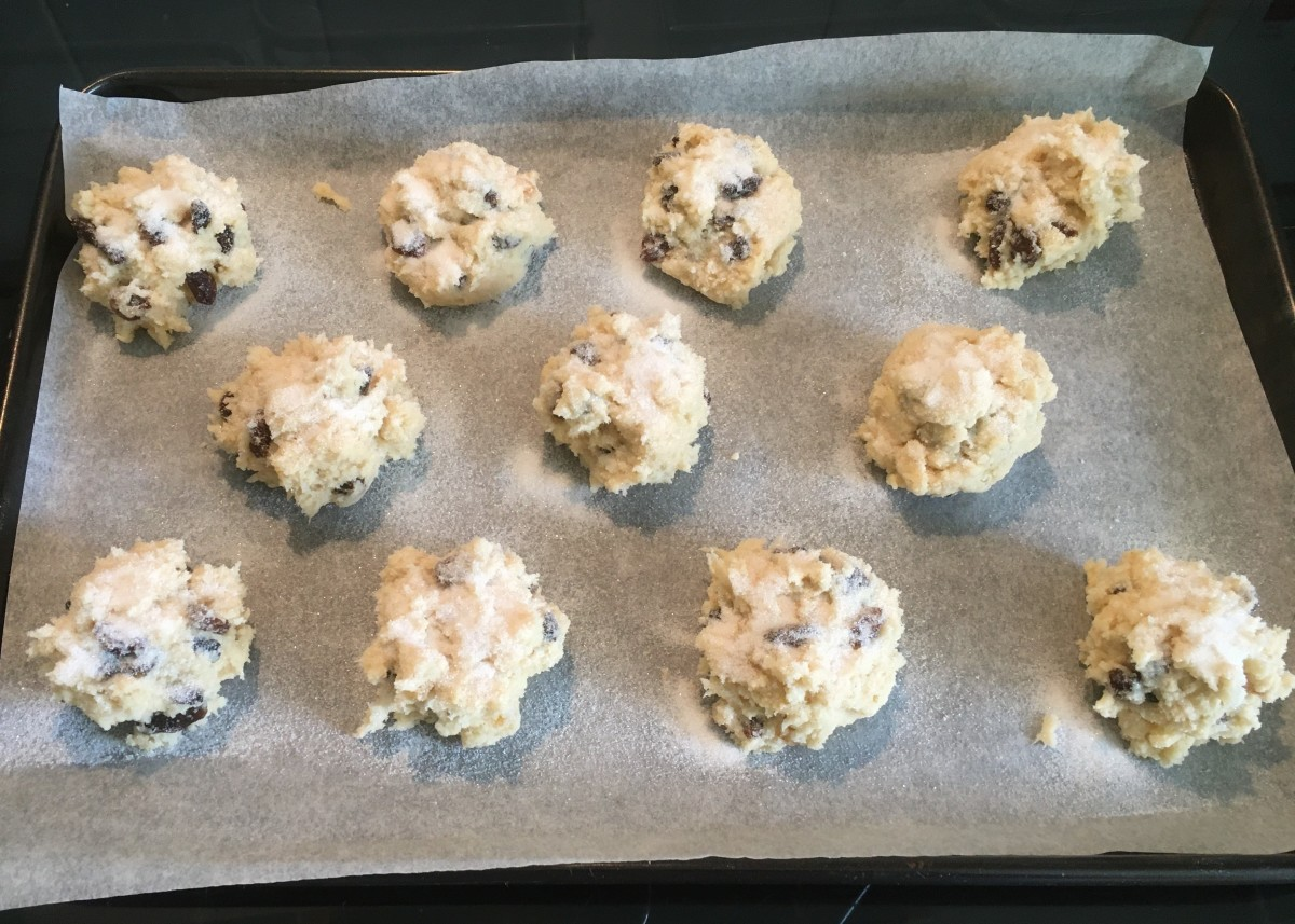 Uncooked rock cakes spaced out on a baking sheet lined with baking parchment. Ready for the oven.