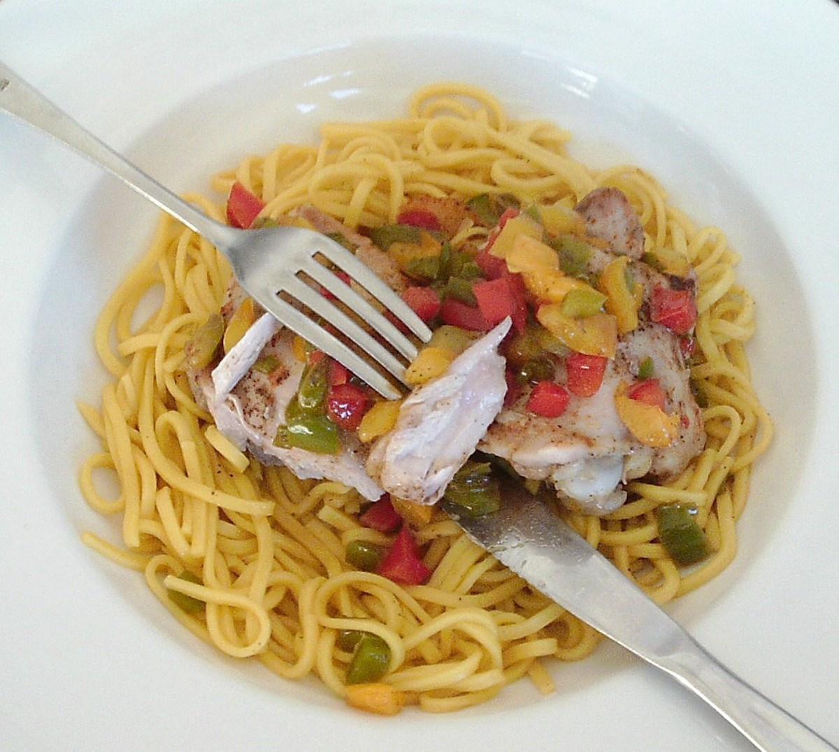 Chicken thighs baked with spices and bell peppers are served on a bed of turmeric spiced egg noodles