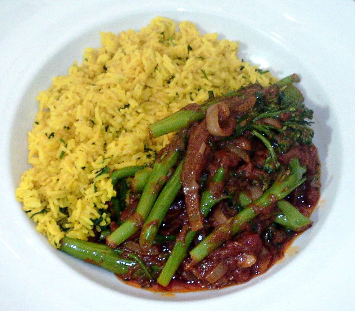 Curried tenderstem broccoli is served with a bed of turmeric and herb rice