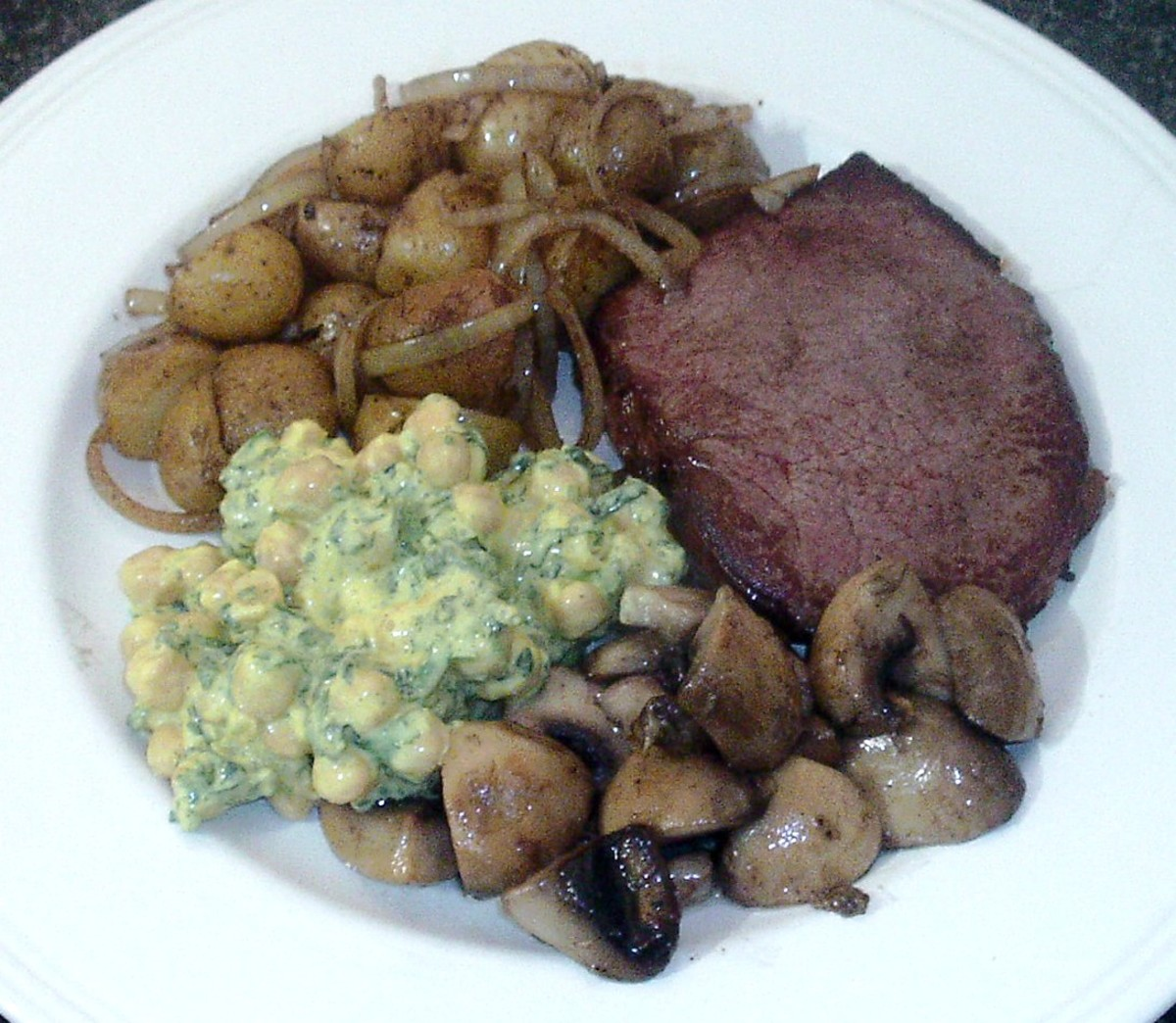 Steak and accompaniments are arranged on serving plate
