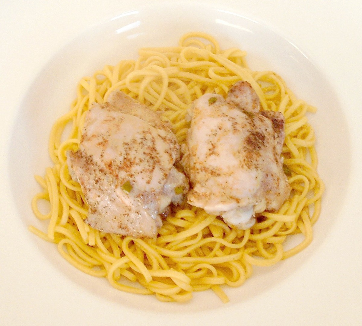 Chicken thighs are sat atop egg noodles