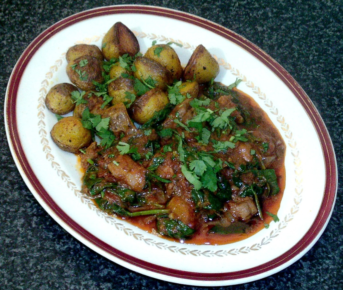 Spicy chicken and spinach curry is served with turmeric spiced roast potatoes