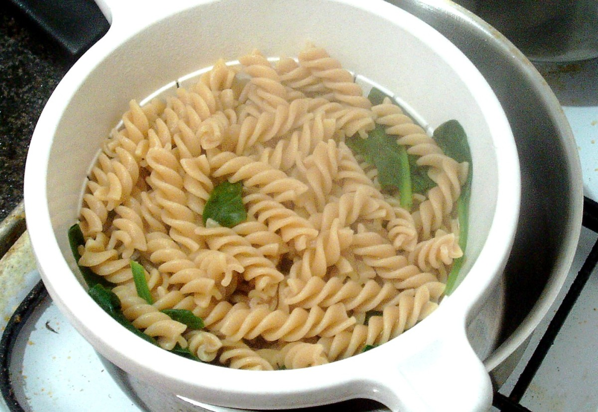 Drained pasta and spinach is left to steam