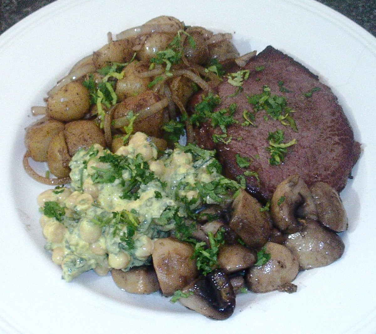 Steak is fried with potatoes and onions fried in its juices, garlic mushrooms and a spicy chickpeas salad