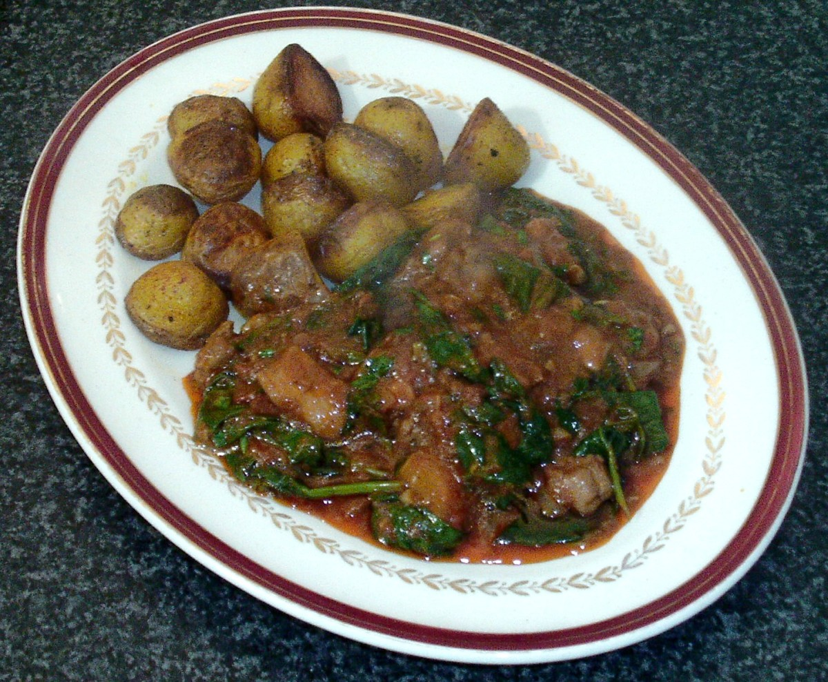 Chicken and spinach curry is plated with roast potatoes on the side