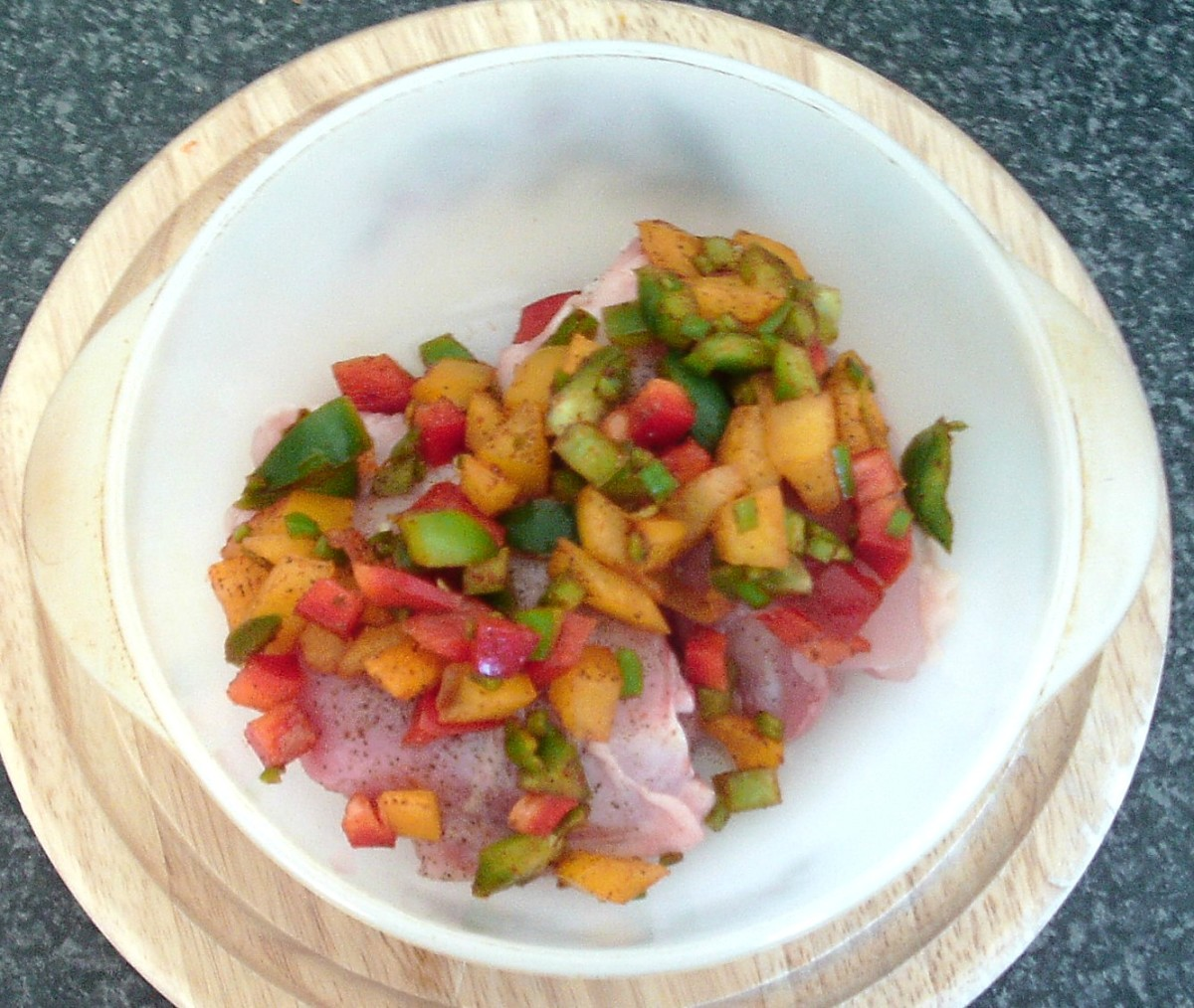 Diced bell peppers are arranged on skinned chicken thighs