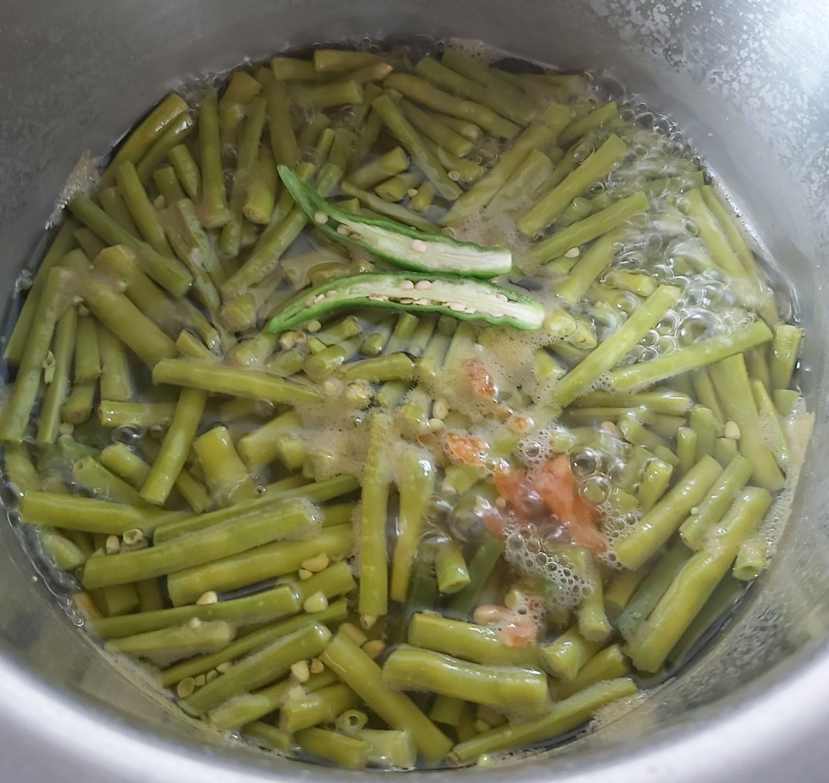 When the long beans are cooked, add 1-2 slit green chilies and 1-2 teaspoons of jaggery. Bring this to a boil.