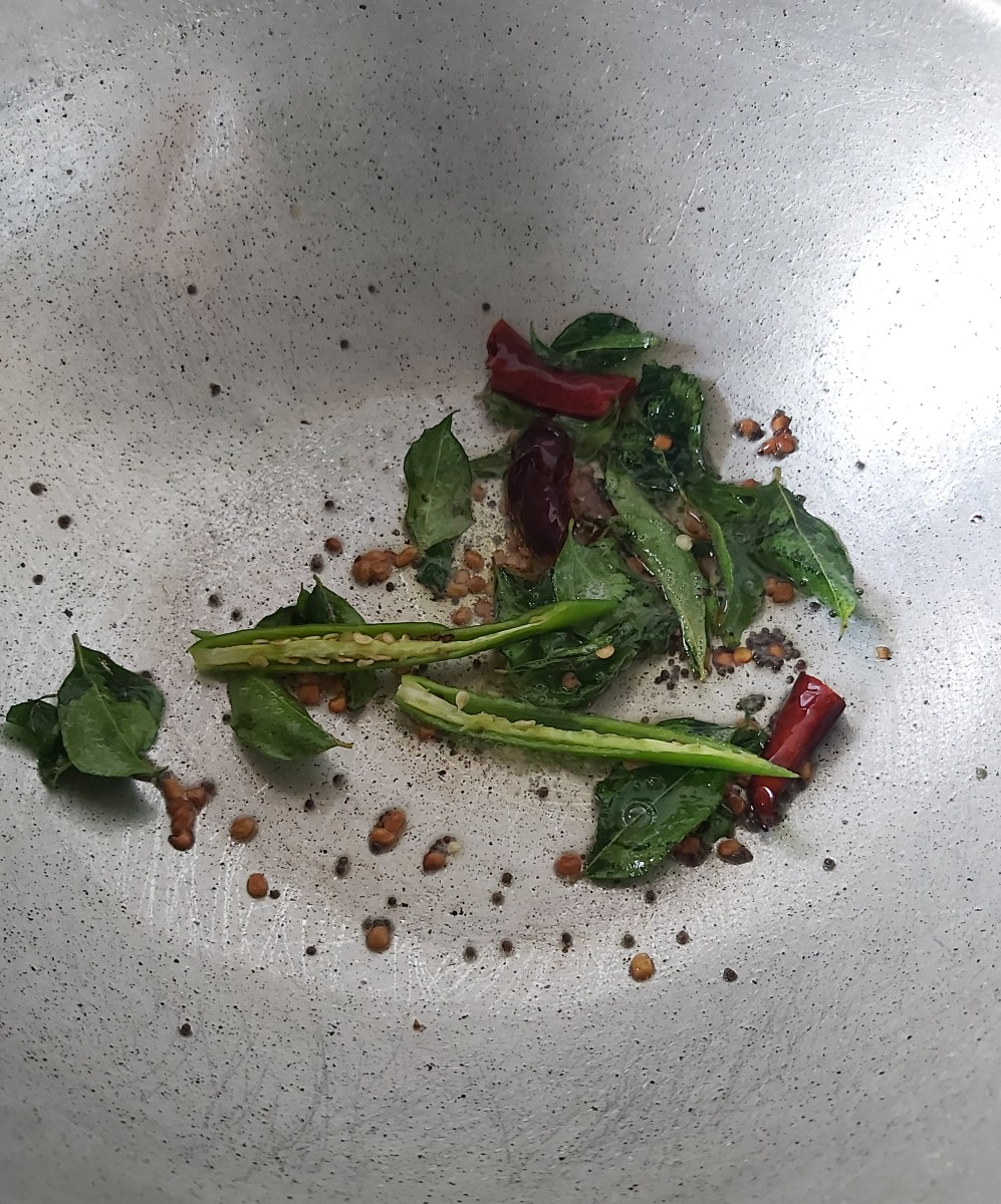 Add the fenugreek seeds (methi), broken red chilies and curry leaves. Fry and add the green chilies. Saute until the red chilies turn crisp.