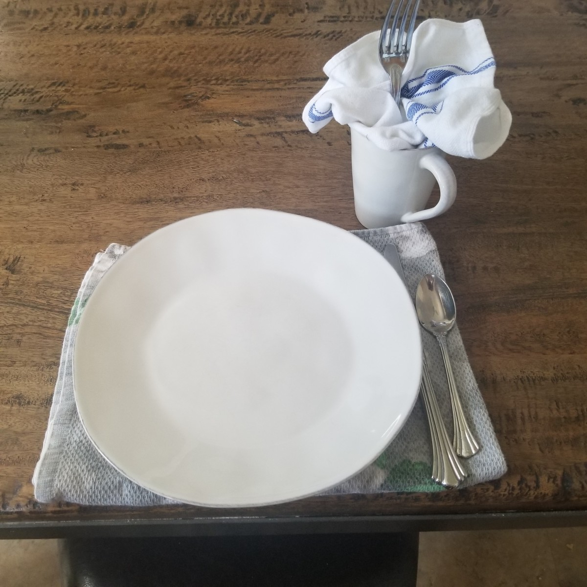 Here a dish towel doubles as a placemat, and another one is tucked into a cup to use as a napkin.