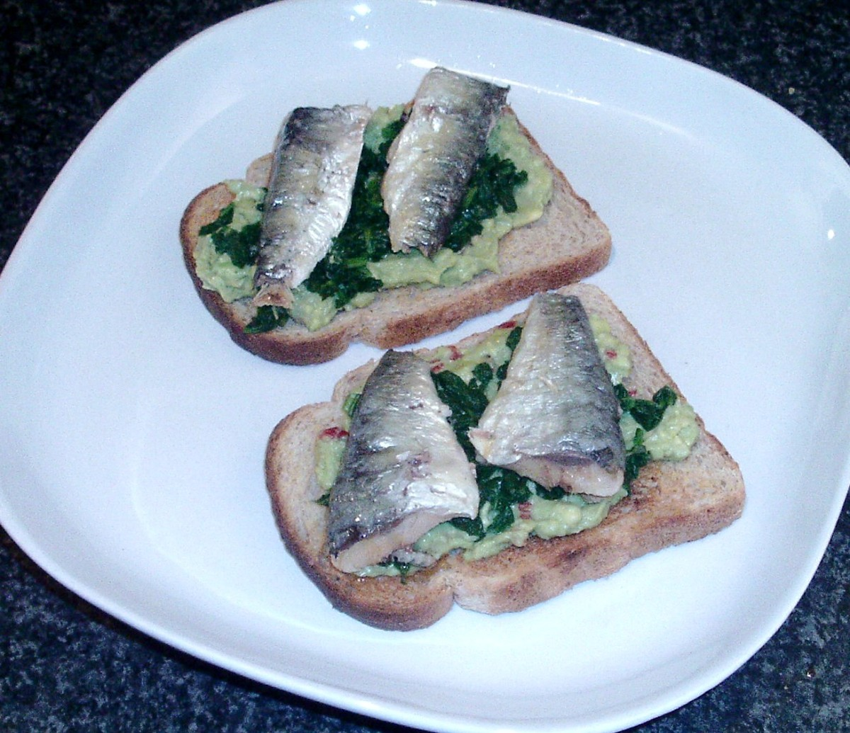 Sardines on toast with guacamole and spinach