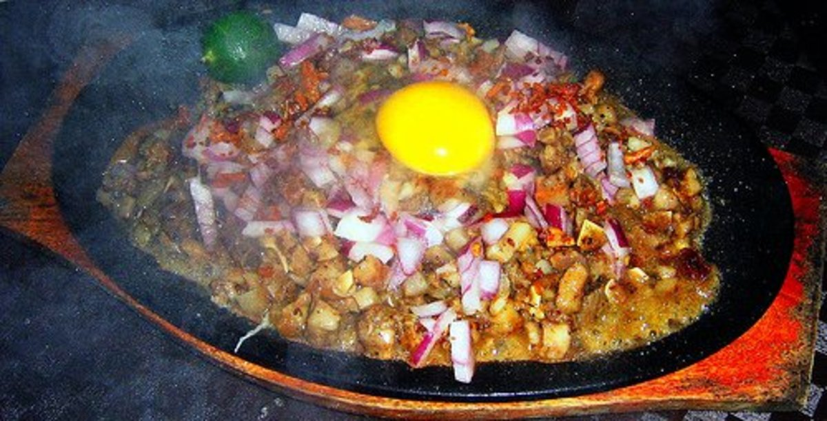 Sizzling hot platter of pork sisig with a whole raw egg on top (photo courtesy by vintagetei from Flickr).