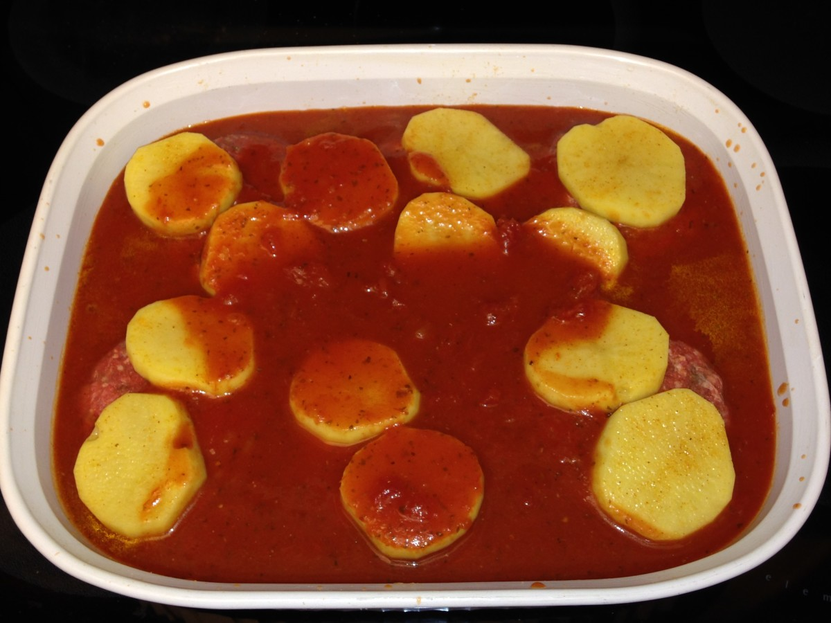 Pour diluted tomatoes over meat and potatoes.  Ready for the oven!