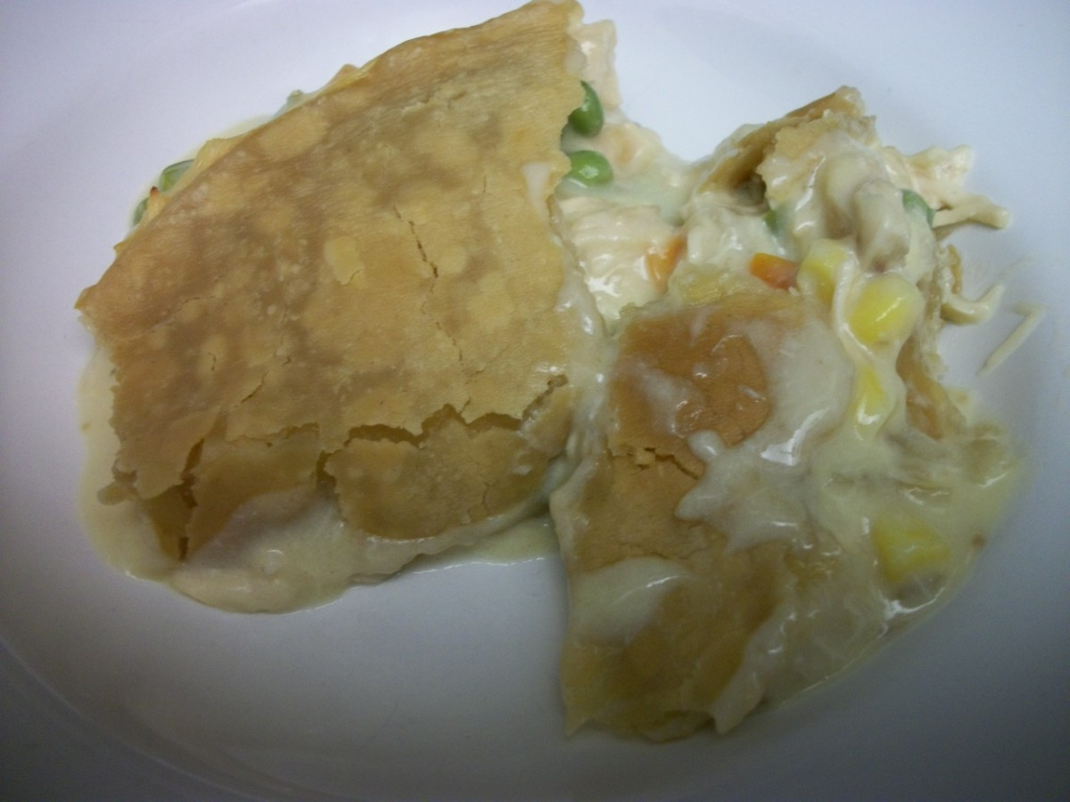 Classic chicken pot pie, family style, with potatoes, corn, carrots, and peas.