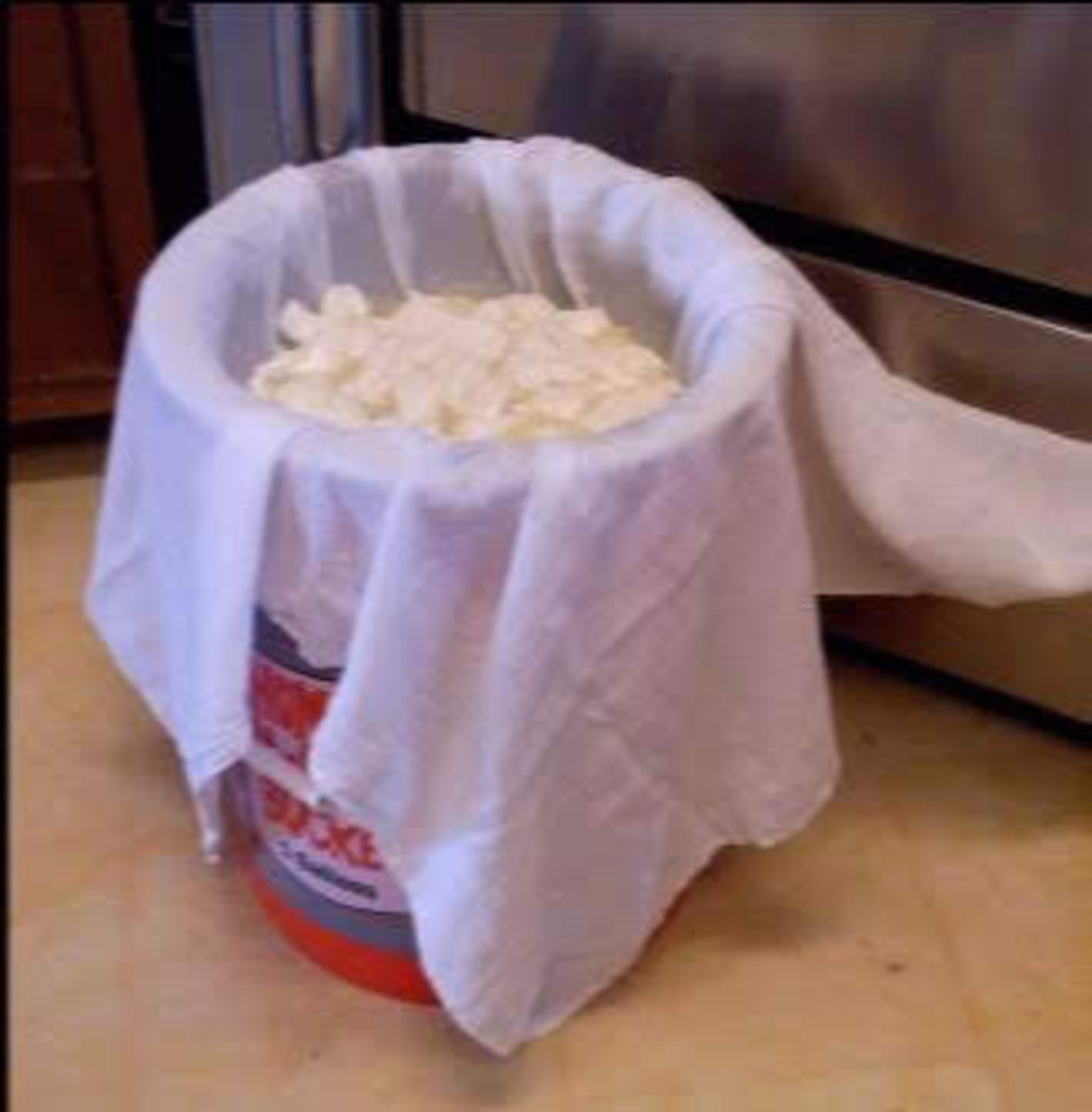 Drain the cheese over a colander lined with a tea-towel draped into it, fitted into a 5-gallon bucket.