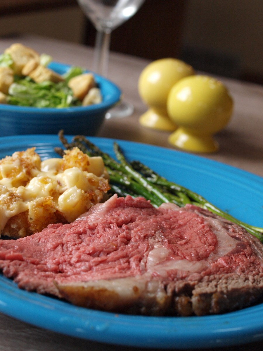 A plated prime rib for Christmas dinner with asparagus, potatoes, and Caesar salad.