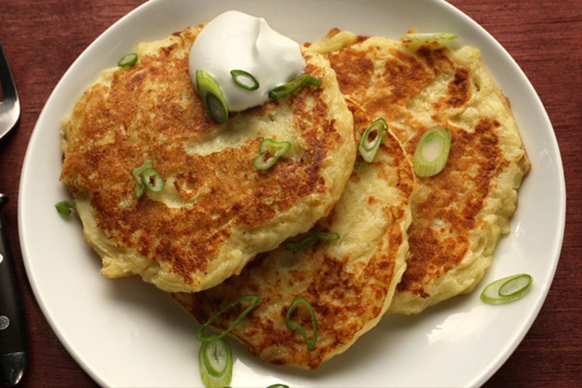 This is our favorite way to serve potato pancakes: with a little chopped green onion and sour cream.