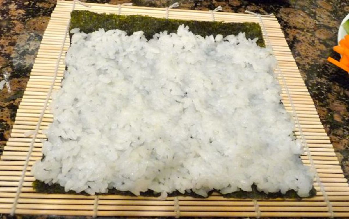 Press down the rice evenly, making sure not to tear the nori. Leave a 1 inch gap with no rice at the top.