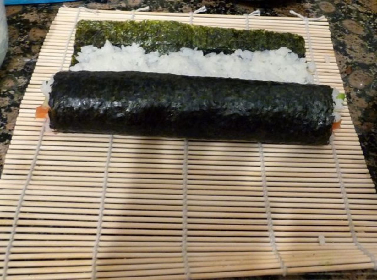 Fold the bottom of the nori over the fillings firmly. Then roll it the rest of the way and seal by wetting the nori with water.
