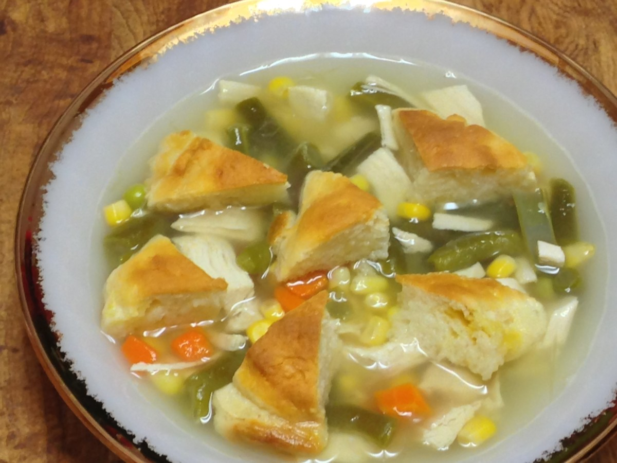 "Chicken & ""dumpling"" soup with diced chicken, mixed vegetables, chicken broth, and biscuit ""dumplings."""