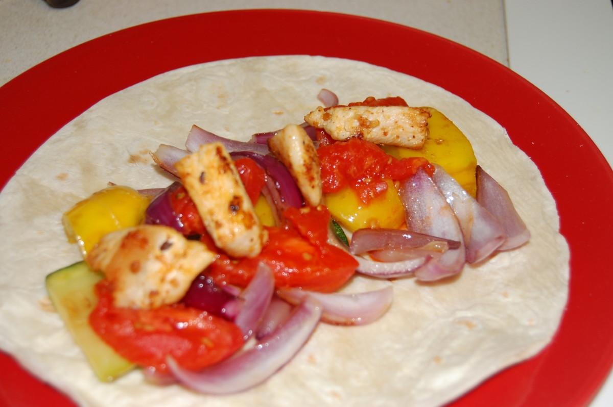 Fajita with sauteed zucchini, yellow pepper, purple onion, tomato, and chicken