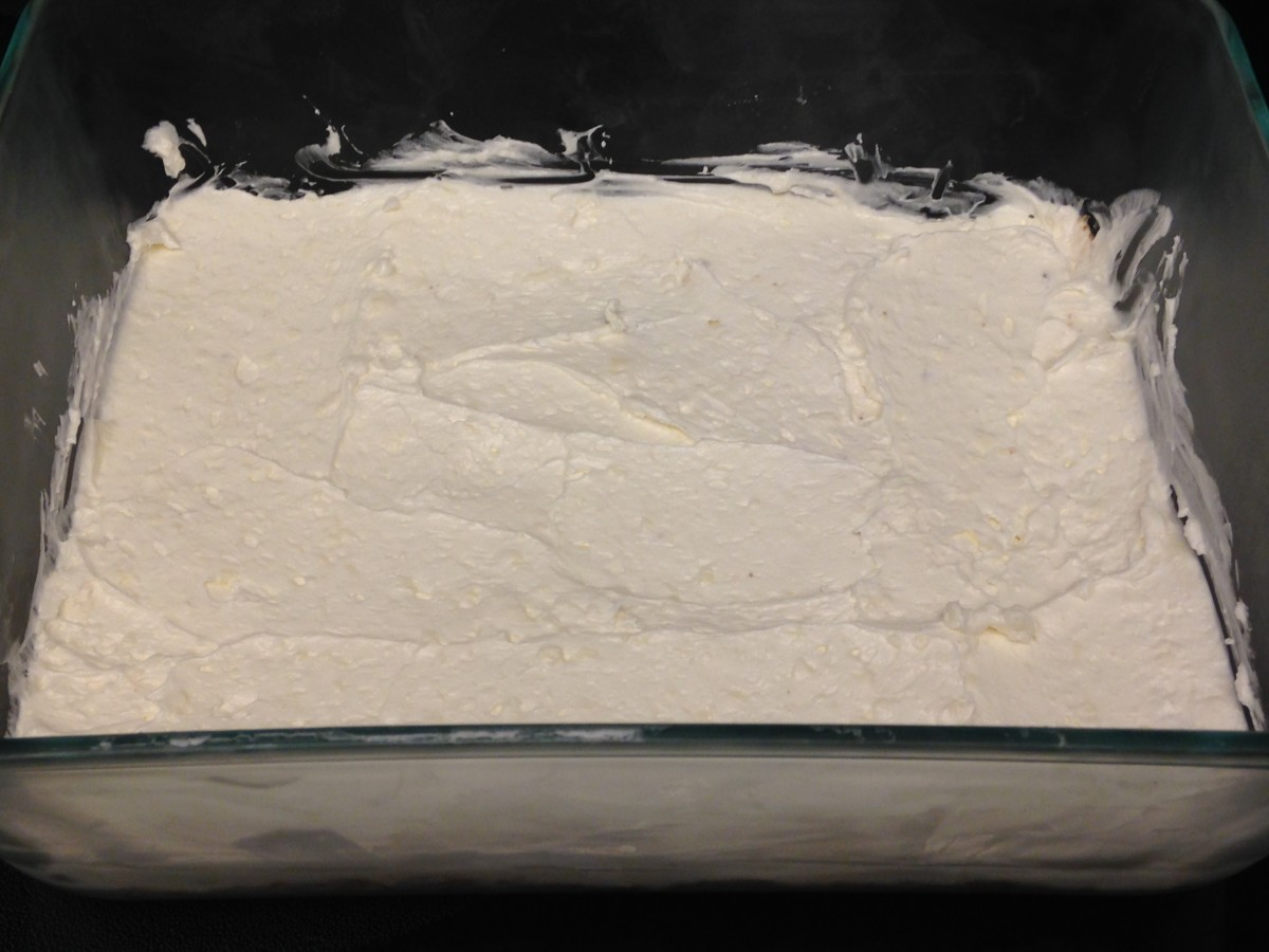 Layer 2 is made with cream cheese, powdered sugar, and Cool Whip.